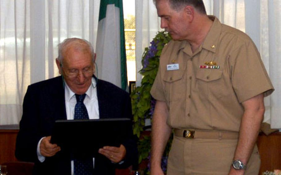 Capt. Philip Valenti, Fleet Industrial Supply Center Sigonella commanding officer, presents Sam Barbagallo with an honorary ownership plaque during Barbagallo's retirement ceremony Oct. 28. Barbagallo worked at the base for more than 40 years.