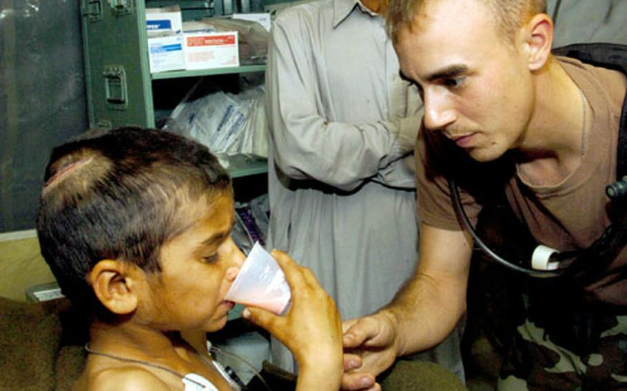 1st Lt. Tory Marcon helps Riaz Sharif drink the only food tetanus patients at the 212th MASH can manage to swallow because of muscle spasms: a powdered milkshake from the MREs.