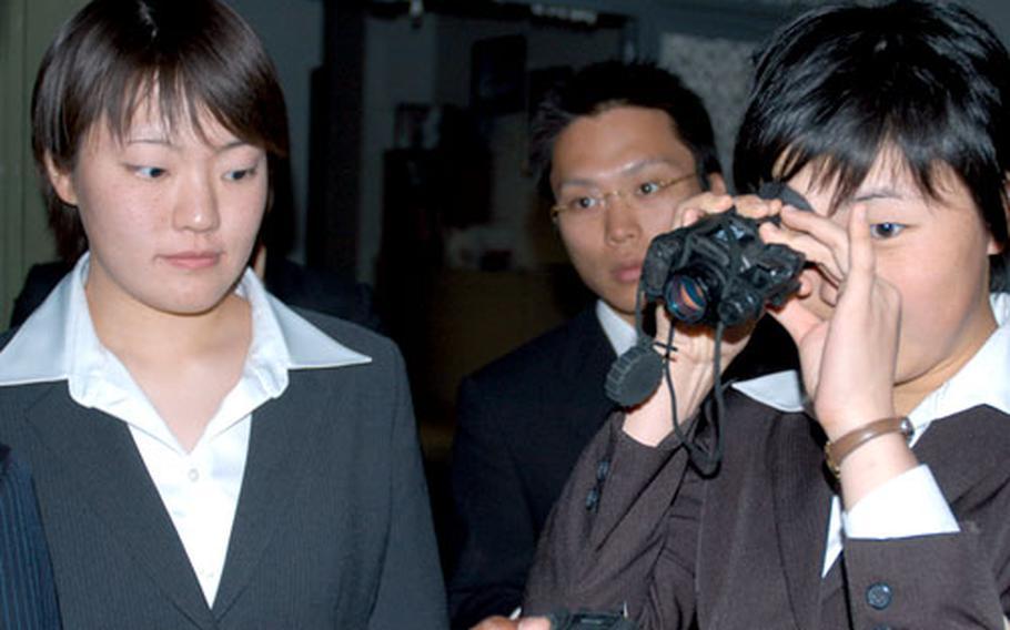 Manami Sasaki, right, and Yuri Sotoyama took turns looking through night vision goggles while visiting 35th Security Forces Squadron at Misawa Air Base, Japan, on Monday.