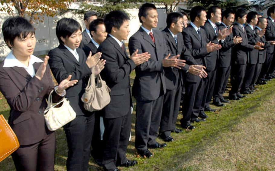 Japanese National Police cadets from the Aomori Prefecture police academy applaud after watching a military working dog demonstration outside the 35th Security Forces Squadron at Misawa Air Base, Japan.