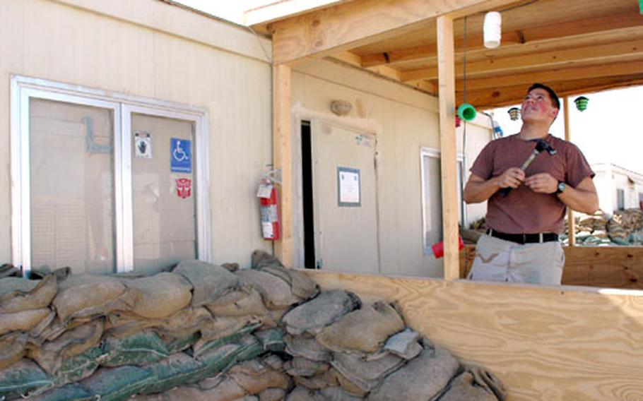 Sgt. Kevin Wigger of Fruitport, Mich., shows off the porch he built as an addition to his living trailer on Camp Warhorse.