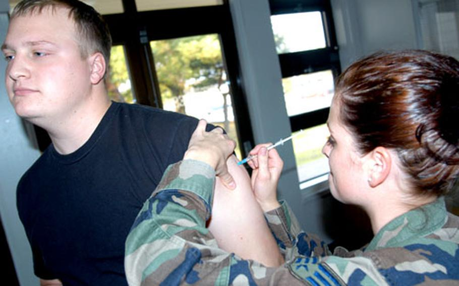 Senior Airman Gina Shinner, a medical technician at Misawa Air Base, Japan, pokes Airman 1st Class Matthew DeVere with the influenza vaccine at Misawa's Potter Fitness Center on Friday. Though the shot isn't protection against avian flu, health officials recommend the immunization especially in light of a potential bird flu pandemic.