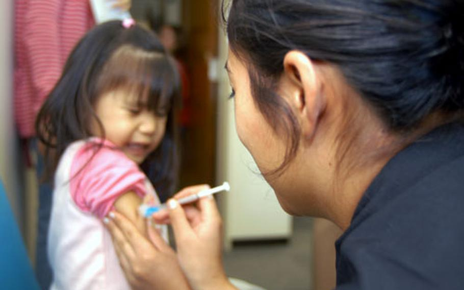 Seaman Christine Lowe, a hospital corpsman at Yokosuka Naval Hospital, Japan, makes a quick jab on 3-year-old Jenelle Ysip. Ysip was, one of 200 people who turned out Wednesday to get vaccinated for the flu virus.