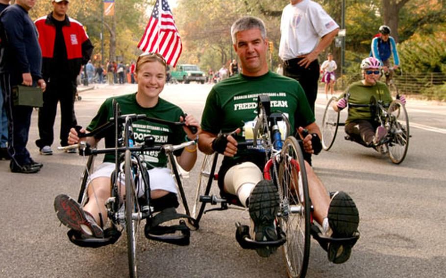 Retired Army 1st Lt. Melissa Stockwell, left, and Army Staff Sgt. Joe Bowser check out their hand-crank chairs before a training session Saturday in New York City's Central Park. The two are members of the Achilles Track Club and will be competing in Sunday's New York City Marathon.