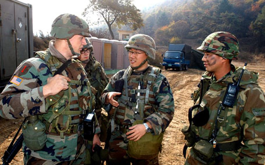 6th Battalion, 37th Field Artillery Regiment soldier Spc. Jesse Specht, left, discusses radio frequencies with a ROK Army soldier, right, with the help of a Korean Augmentee to the U.S. Army, center.