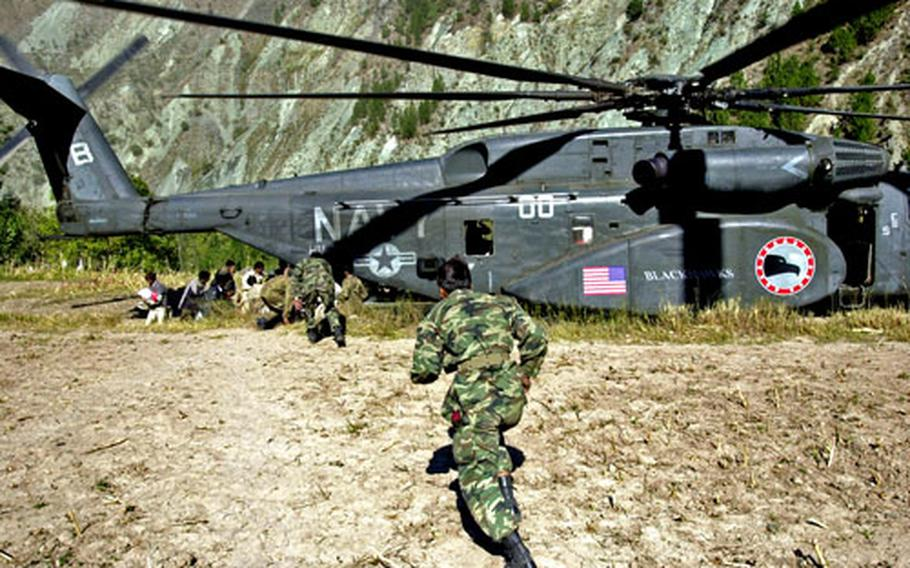 Pakistani soldiers run to a U.S. Navy MH-53 that landed Sunday to deliver relief supplies to the earthquake effected village of Paras, Pakistan.