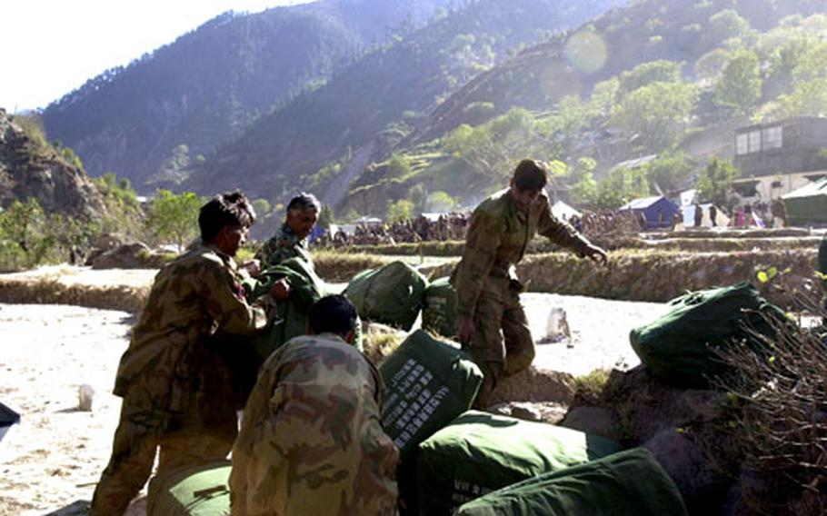 Pakistani soldiers pull tents off an Army Chinnok helicopter Sunday in Paras, Pakistan.