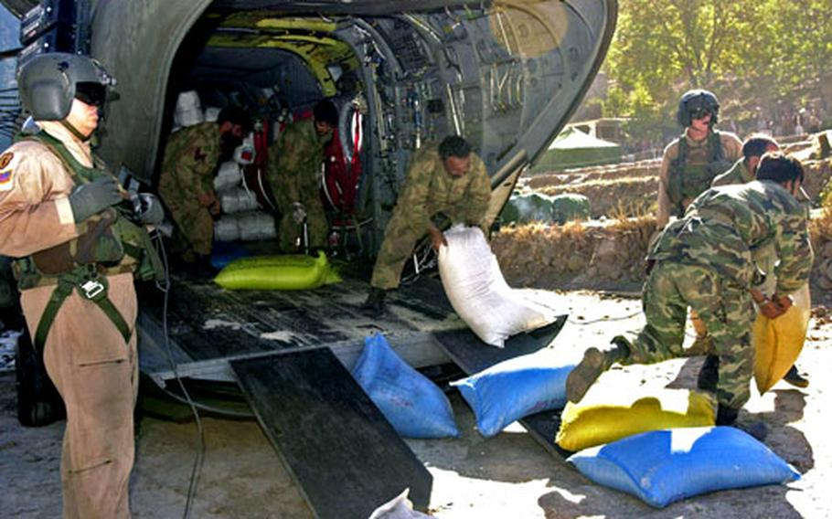 Pakistani soldiers pull bags of rice off an Army CH-47D Sunday as crew chiefs Spcs. Stephen Bergstrom, left, and Scott Madden, right rear, watch in Paras, Pakistan.