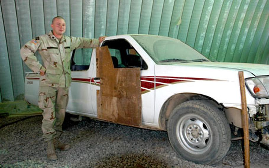 Sgt. Gordon Truett stands next to an Iraqi Army pick-up truck that he is using in designing vehicle armor that could help protect the local forces from roadside bombs.