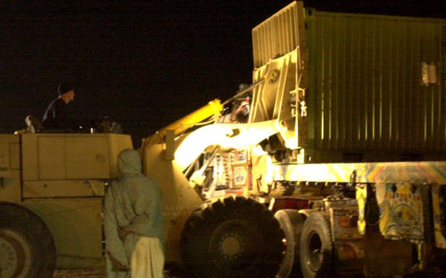 """A shipping container is loaded onto a local """"jingle truck"""" at Chaklala Air Field, Pakistan."""