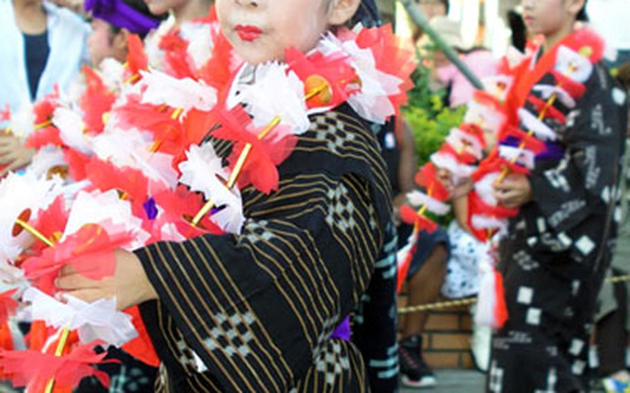 A young girl in traditional Okinawan folk costume participates in the carnival.
