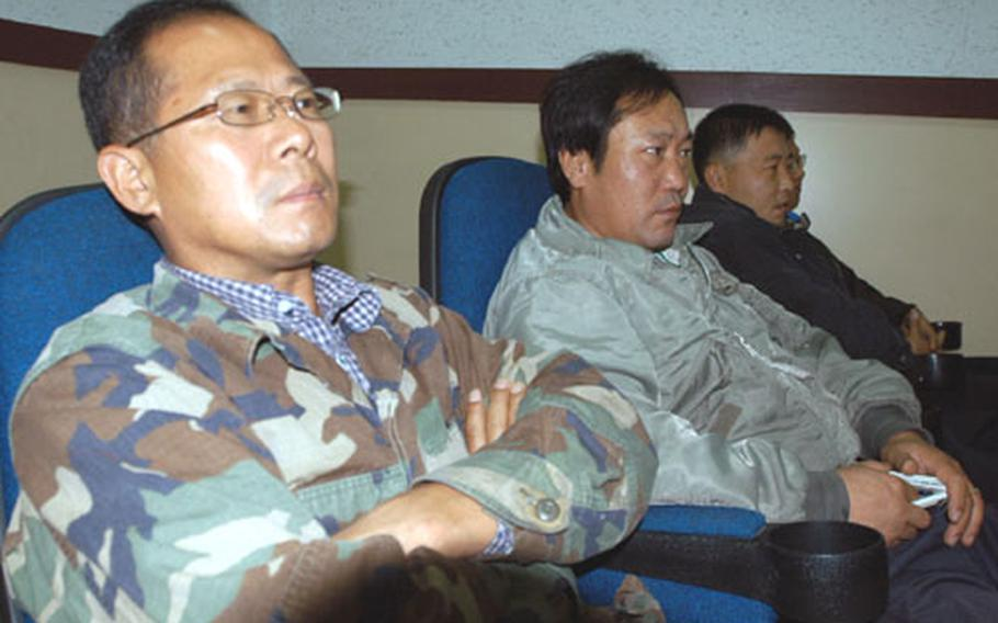 South Korea base workers listen to Area I commander Col. Forrest R. Newton at Camp Red Cloud, South Korea, on Tuesday.