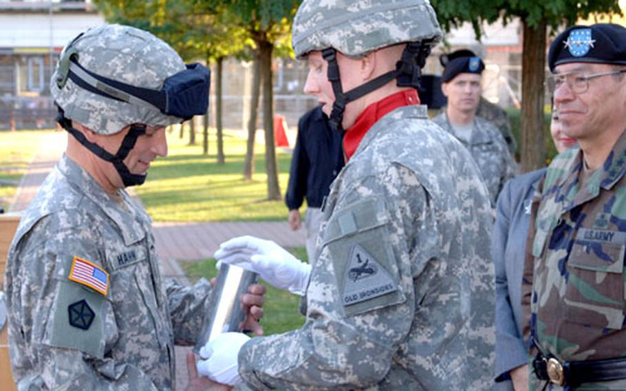 Maj. Gen. Daniel A. Hahn accepts a presentation artillery shell from Pfc. Jeremiah Johnson of the corps' Battery C, 1st Battalion, 94th Field Artillery, signifying the cannon salute Johnson and his fellow soldiers fired in honor of Hahn's promotion.