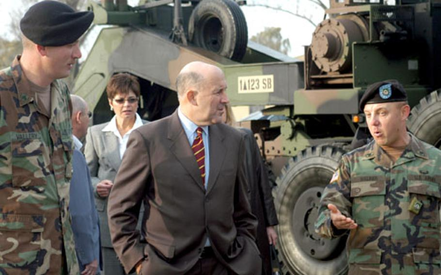 Wisconsin Gov. Jim Doyle chats with Army Sgt. Robert Vallery, left, and Staff Sgt. Arthur Walker during a Wednesday visit to Dexheim, Germany. Doyle, who is on an 8-day trade mission to three European countries, stopped in Dexheim to dine with soldiers from Wisconsin and check out heavy equipment transport trucks manufactured in Oshkosh, Wis.