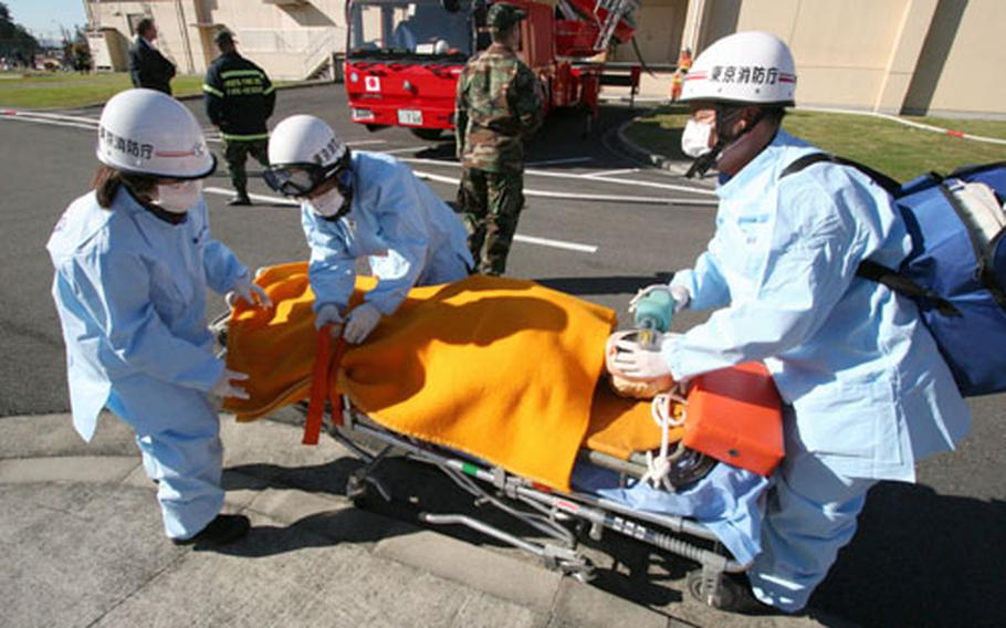 """Members of the Tokyo Fire Department's Fussa station tend to a dummy """"victim"""" during Wednesday's joint fire and rescue exercise at Yokota."""