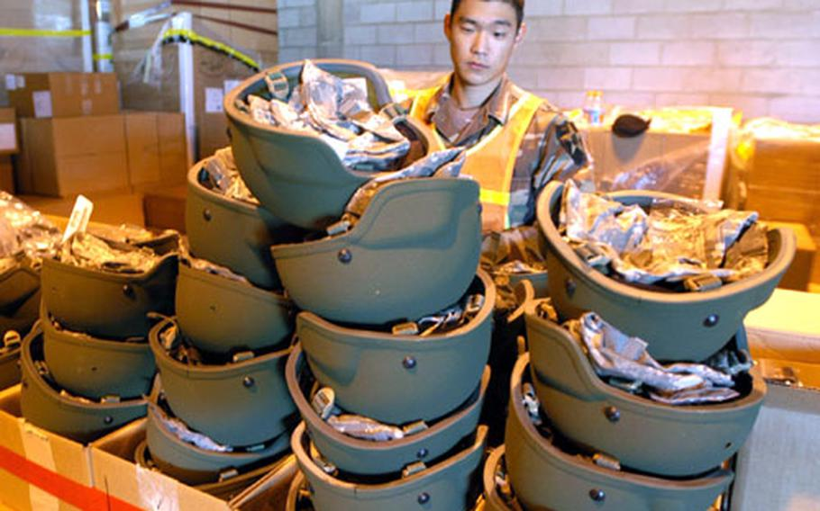 Cpl. Choi Sung-bae, 23, of Seoul, a Korean augmentee to the U.S. Army serving with 1st Battalion, 72nd Armored Regiment, prepares to fit soldiers with new Kevlar helmets at Camp Castle on Tuesday.