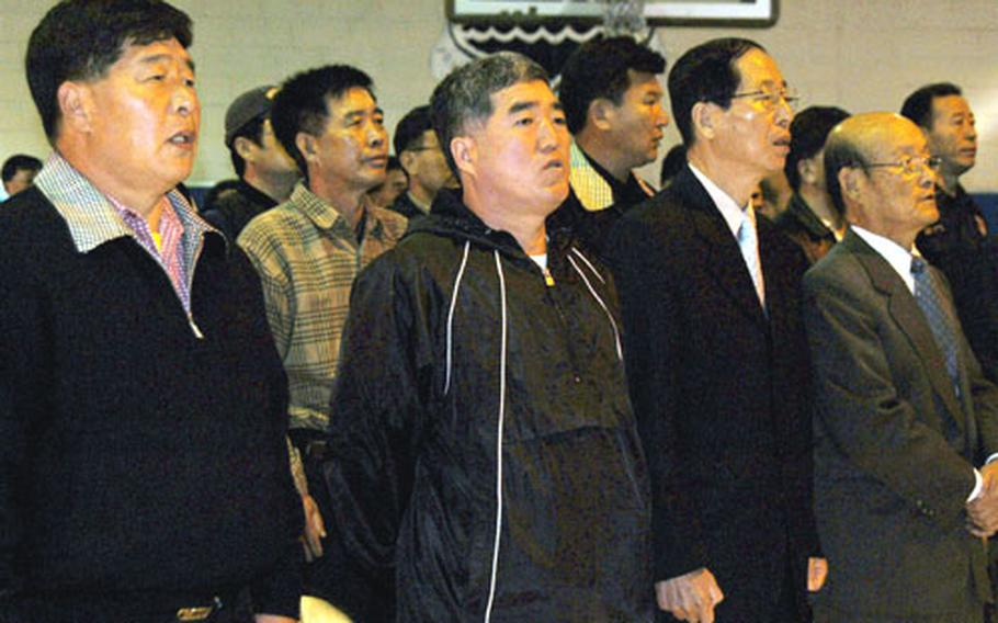 South Koreans who lost their jobs when Camp Colbern closed sing their national anthem Wednesday during a ceremony at Colbern recognizing their years of service. The camp closed in October, and the U.S. soldiers there moved to Camp Stanley near Uijeongbu, South Korea.