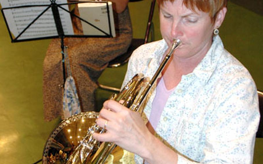 Christel Breeze, front, a French horn player and substitute teacher, also rehearses, along with orchestra manager Mutsumi Hasuda.