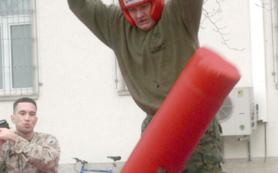 Cpl. Paul Mahneke lowers the boom on an opponent during the pugil sticks battle.