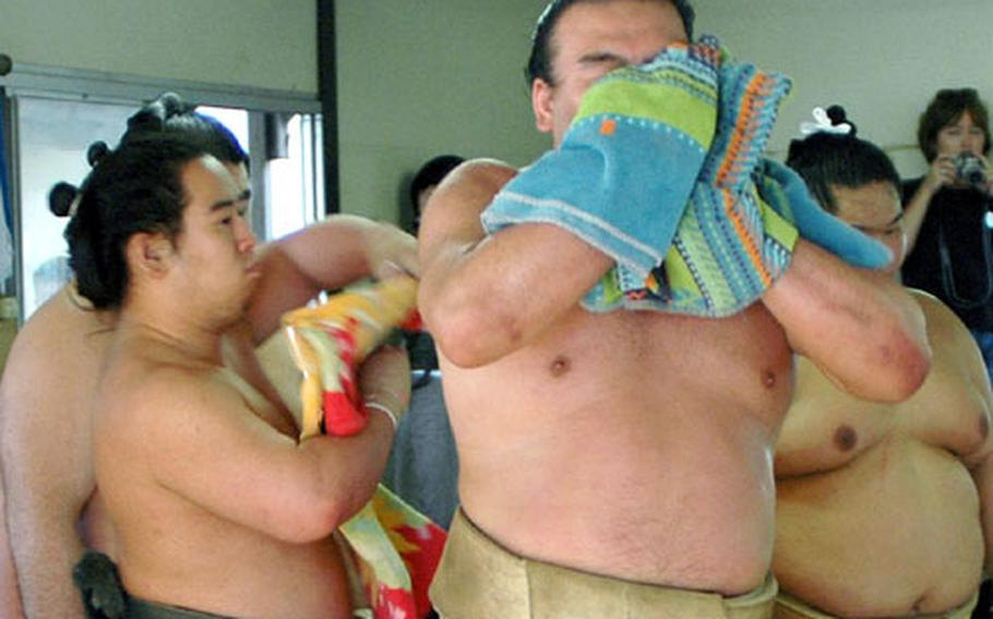 Grand Sumo East Maegashira #9 Takamisakari wipes sweat from his face and neck after several hard practice matches Saturday against up-and-coming Hakuho, a 20-year-old Mongolian, at Azumazeki Beya (sumo stable) in Fukuoka.