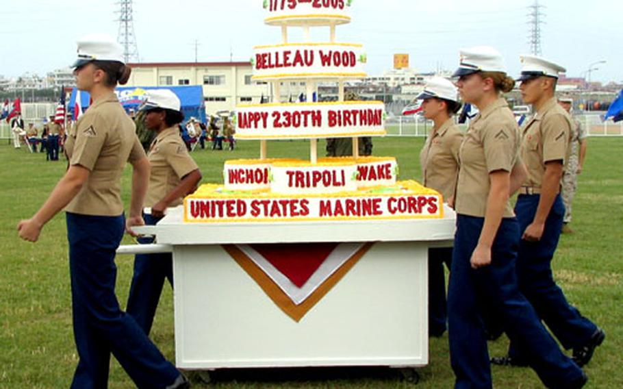 Marines carry the birthday cake onto the parade deck at Camp Foster on Thursday. Printed on the cake were names of some of the most renowed battles Marines have taken part in over the years.