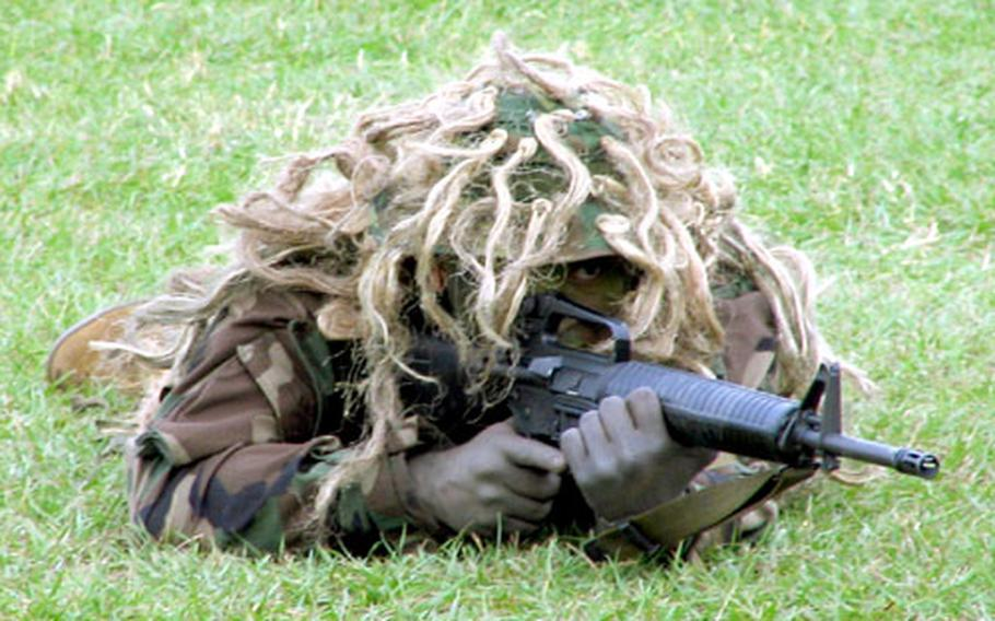 A Marine sniper blends in with his surroundings during a uniform pageant at Thursday's celebration of the Marine Corps' 230th birthday on Okinawa.