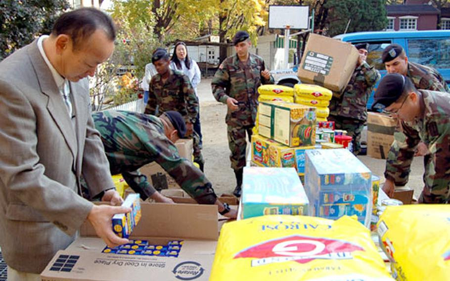 Park Heung-sik, director of Namsan Orphanage in Seoul, looks through some of the donated food as soldiers from the 94th Military Police Battalion arrange the goods.