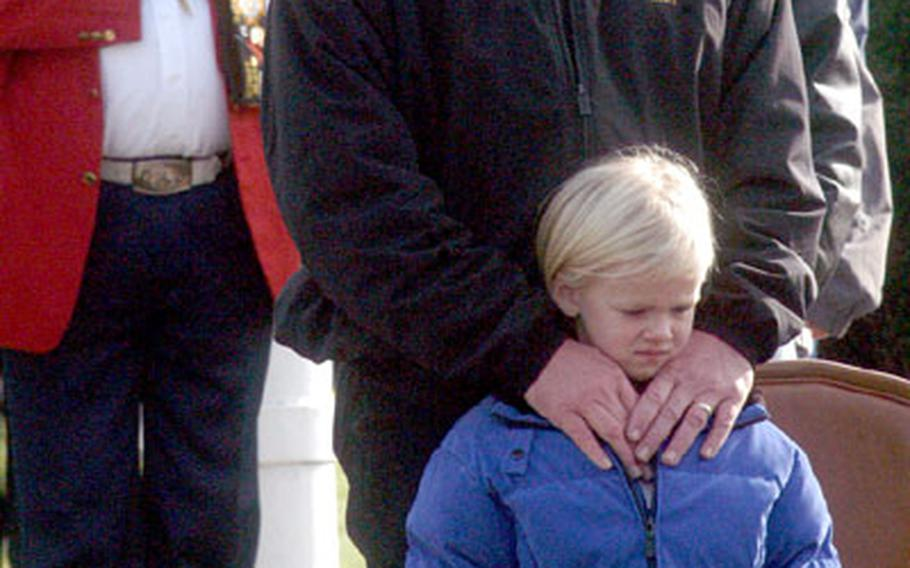 Observers bow their heads during the opening prayer at the Veterans Day observance on Friday at Patch Barracks.