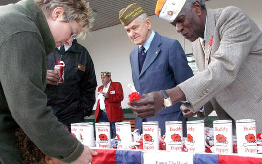Frank De Ciccio, center, and James W. Johnson, right, take donations in exchange for Buddy Poppies on Friday outside the commissary at Patch Barracks. The donations are distributed to needy veterans by the Veterans of Foreign Wars.