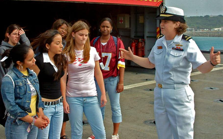 Ensign Katherine Kimsey, the USS Juneau's weapons officer, describes flight deck operations to seniors from Kadena High School during a ship tour Wednesday at White Beach Naval Facility in Okinawa.