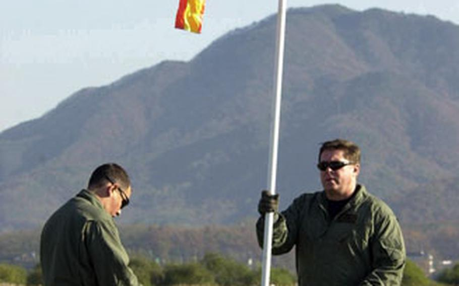 Two U.S. Army Special Forces soldiers set up a windsock before jump training Wednesday at a drop zone near Seoul.