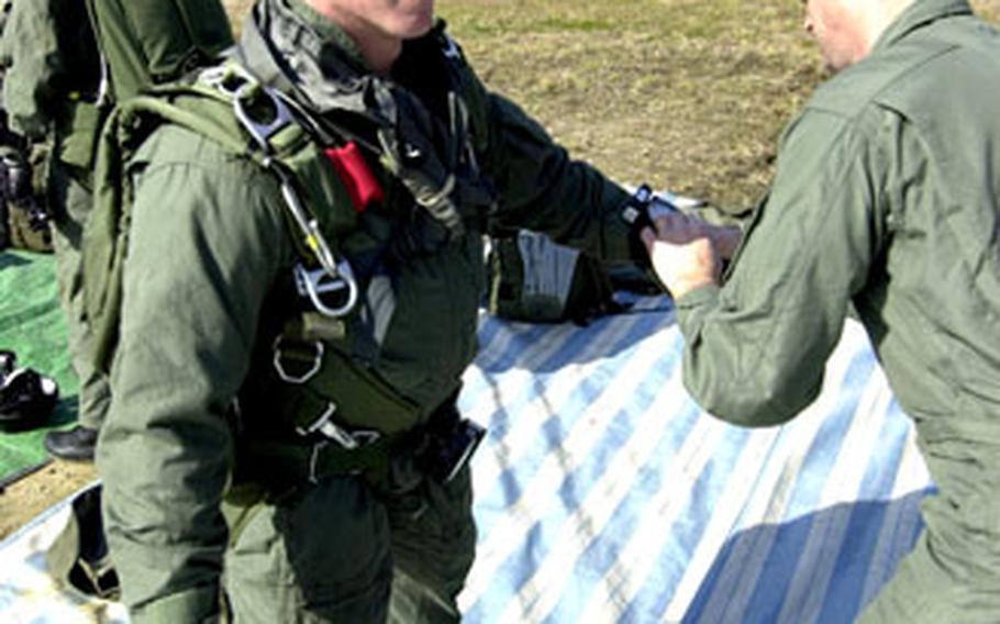 Sgt. Maj. Jack Hagan, right, checks Sgt. 1st Class Jeremy Burke before jump training Thursday.