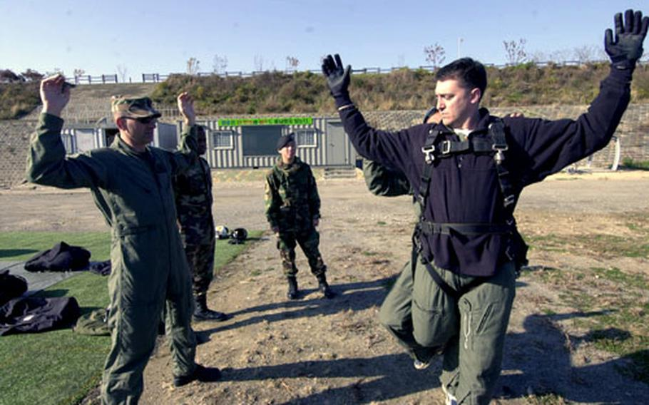 Stars and Stripes Korea Bureau Chief T.D. Flack, right, practices for his first tandem jump Wednesday at a drop zone near Seoul.
