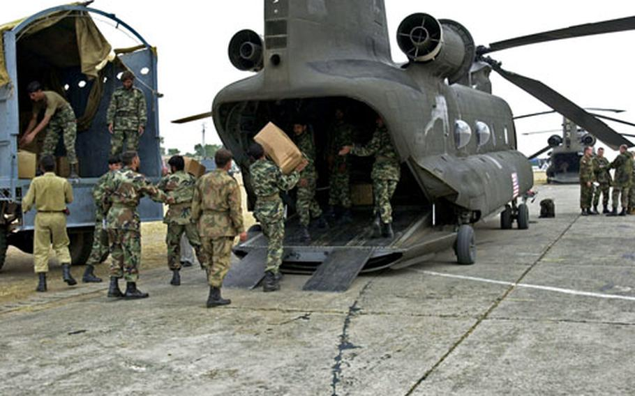 Pakistani soldiers load boxes of clothes, bound for earthquake victims, into the back of a U.S. Army CH-47 Chinook on Chaklala Air Field, Pakistan, on Friday. Weather has been good recently, allowing the helicopters to fly numerous missions each day.