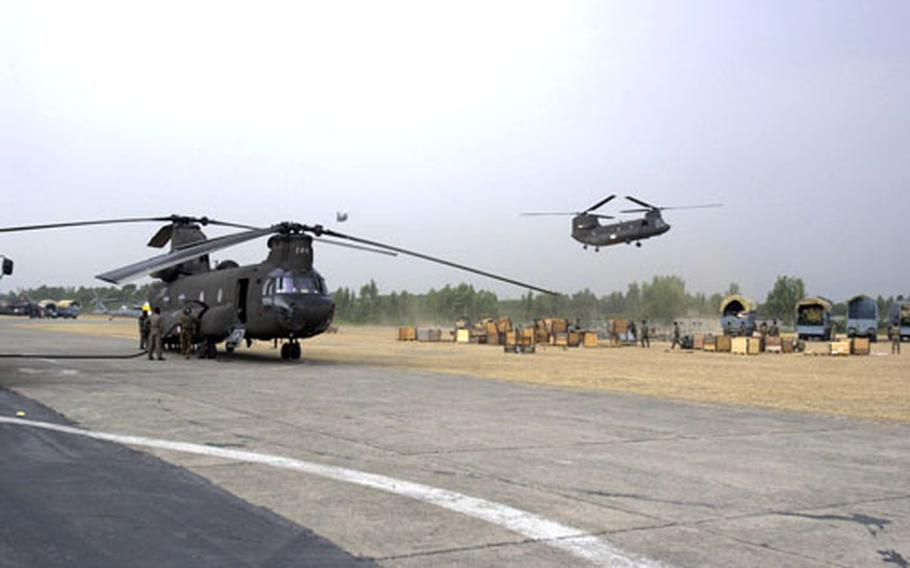 A Chinook is refueled Friday after completing a relief supply mission as two others return to Chaklala Air Field, Pakistan.