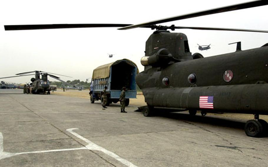 Two Chinooks are loaded with relief supplies at Chaklala Air Field after a mission in Pakistan on Friday.