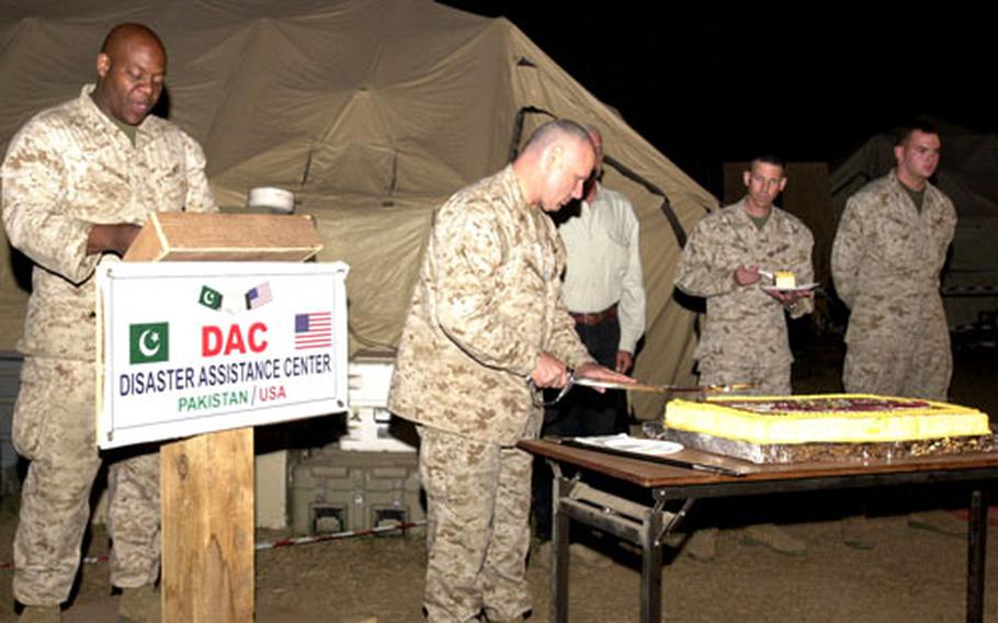 Maj. Grover Wright, camp commandant for the Disaster Assistance Center on Chaklala Air Field, Pakistan, reads about the significance of the cake-cutting ceremony while Col. Mark Losack, deputy commander of the DAC, uses a sword to do the honors Thursday during a celebration of the Marine Corps' 230th birthday.