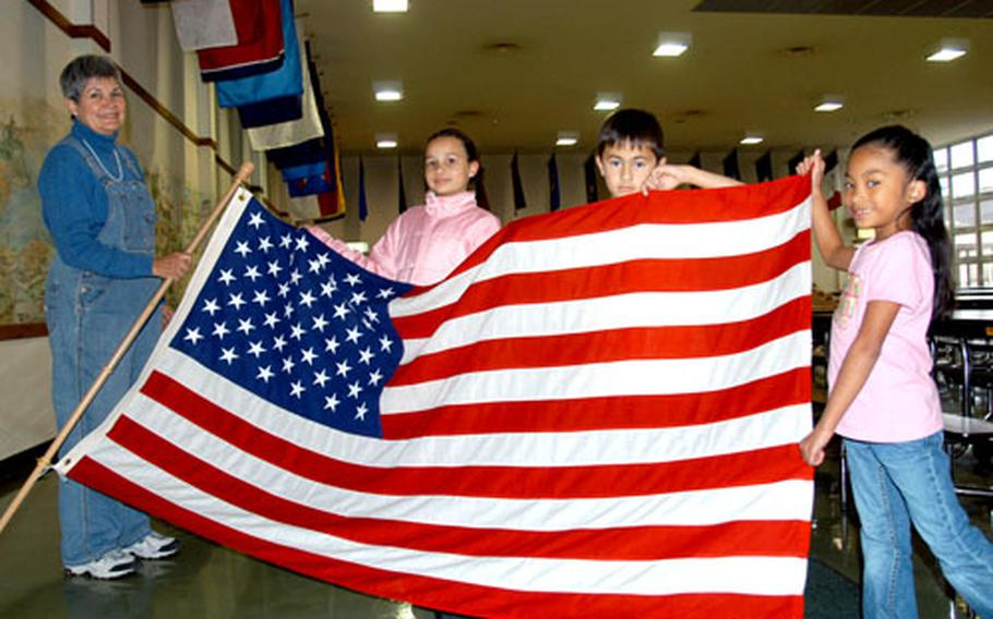 Sollars Elementary School second-grade teacher Elise Henderson and three of her students from last year — from left, Ryann Moyers, Ryan Seau and Tamiyah Kunsman — hold up the U.S. flag Thursday after helping decorate the Misawa Air Base school cafeteria with 50 state flags, the culmination of a two-year class project led by Henderson.