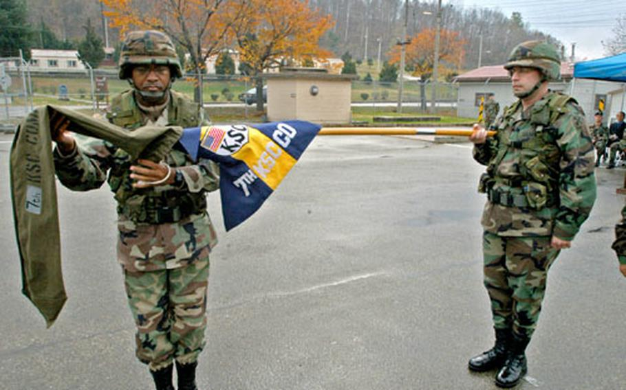 The 7th Korea Service Corps Company colors, held by KSC Battalion commander Lt. Col. Robert J. Paquin, are uncased at Camp Casey, South Korea, on Thursday during a ceremony handing over responsibility for transport of 2nd Infantry Division's heavy equipment as part of the transformation of U.S. forces on the peninsula.