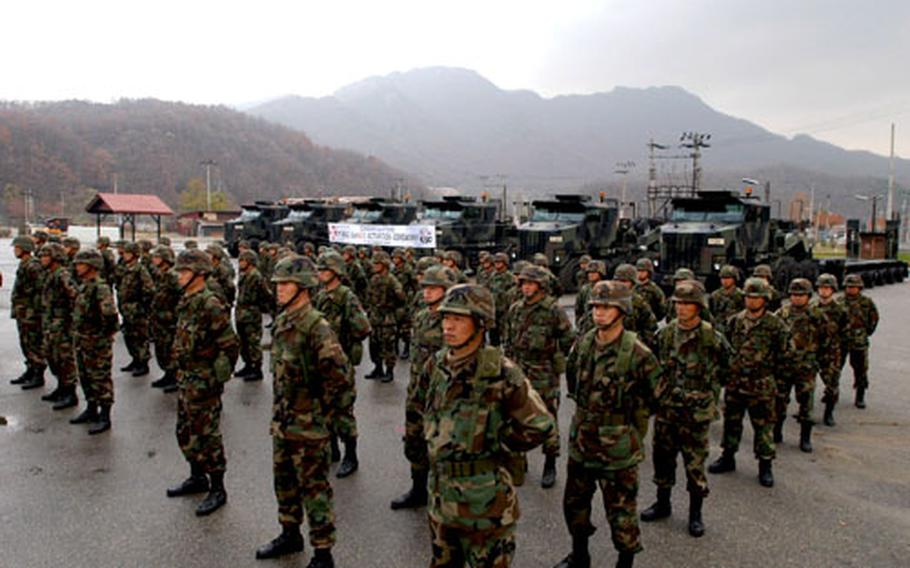 Members of the 7th Korean Service Corps Company stand in formation Thursday with their heavy equipment transporters at Camp Casey.