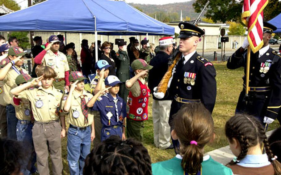 Community members salute as the colors are retired Friday at Friday's Veterans Day ceremony.