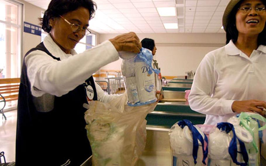 Rosa Rafael helps a customer Thursday at Yokosuka Naval Base's commissary in Japan, where double-bagging is done only by request.