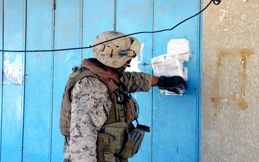Sgt. Scott Wood tears off a freshly posted tract in Husaybah from al-Qaida in Iraq just days after U.S. Marines swept through the city to clear out insurgents.