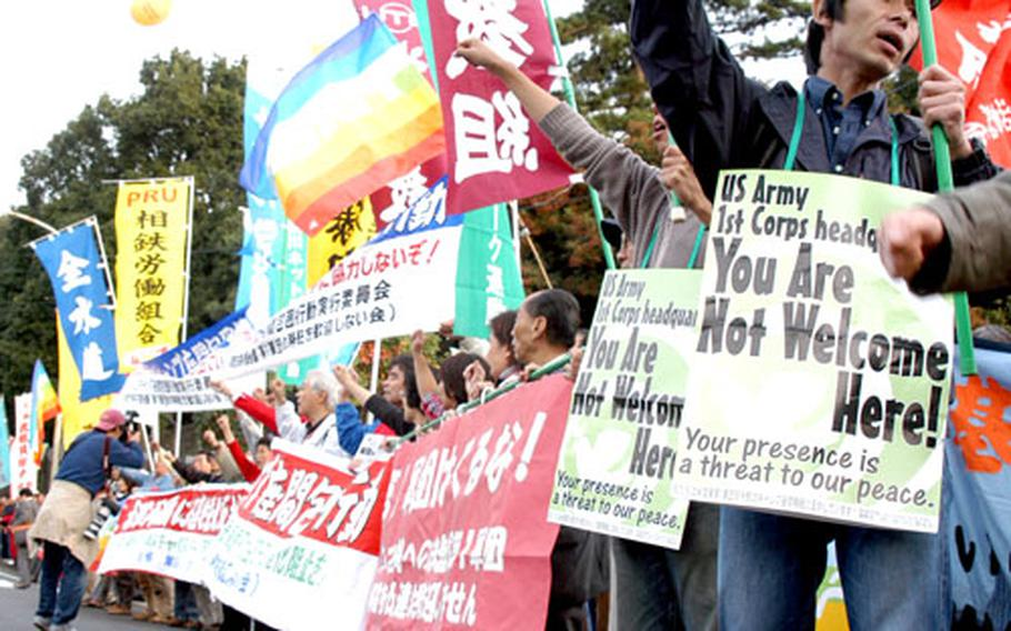 Protesters shout their opposition to an increase of troops at Camp Zama, Japan, on Saturday in front of the base's main gate.