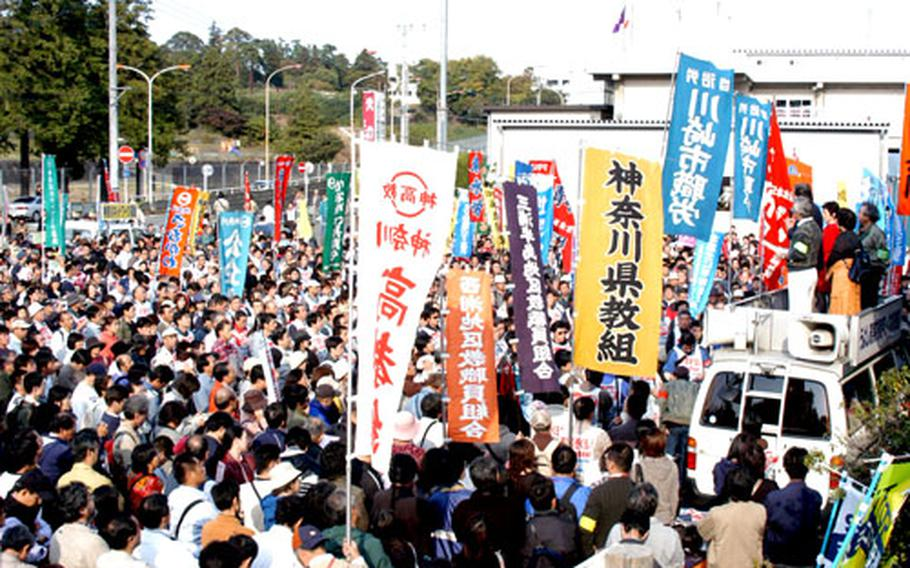 Protesters gather at Camp Zama's front gate Sunday to shout their opposition to any increase of troops at the base on mainland Japan. Organizers said the rally was planned to coincide with the announcement of the interim report on realigning U.S. forces in Japan.