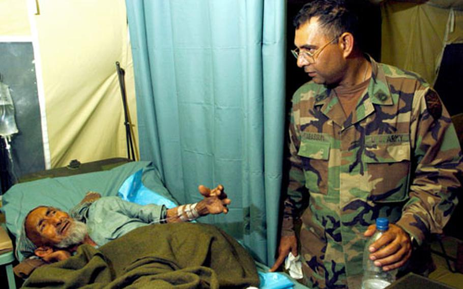 Sgt. 1st Class Mohammad Tabassum, a translator for the 212th MASH, considers the best response to an elderly Pakistani man being treated in the hospital.