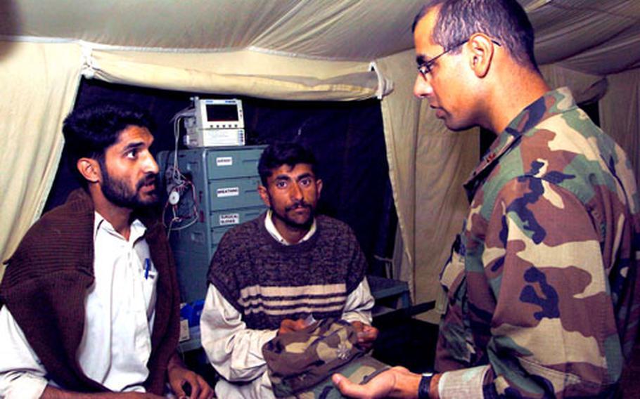 Maj. Fareed Sheik speaks with earthquake victims at the 212th MASH field hospital.