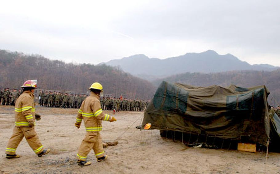 Firefighters prepare to set fire to a tent and its contents Thursday at Camp Casey, South Korea, while members of the Fires Brigade, 2nd Infantry Division look on.