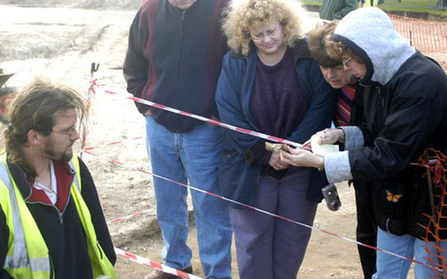 Teachers from RAF Lakenheath schools look at the leg bone of the woman found at the construction site near the base's Gate 2. The bones were being removed by Suffolk Archaeological Service researcher John Craven, left.
