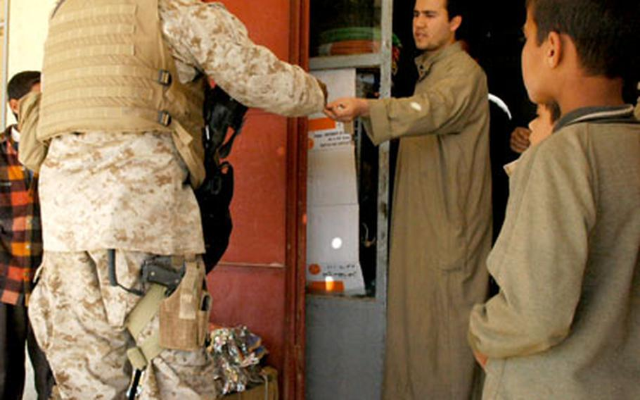 A U.S. Marine interacts with shopkeepers in Husaybah, Iraq, on Tuesday. Providing for the day-to-day needs of local Iraqis here is now a priority for following last week's battles.